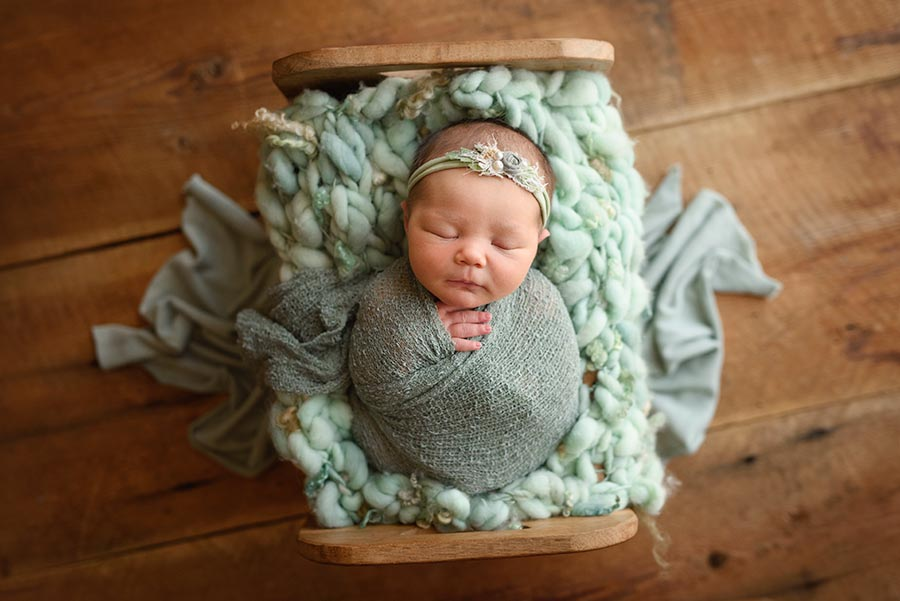 Newborn Baby girl photographed in Denver Studio wrapped in sage and posed in a wooden bed