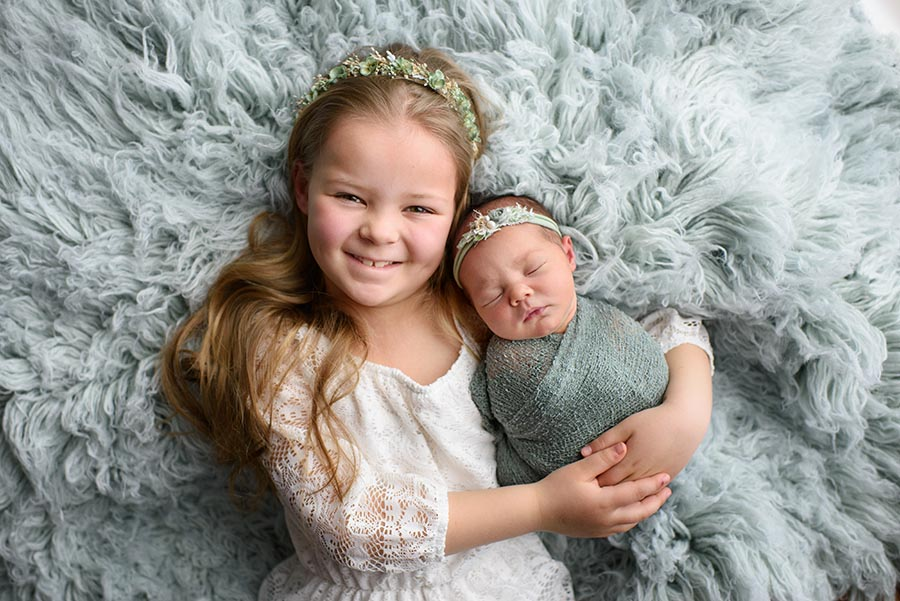 Sisters, newborn photographed with her big sister on flokati
