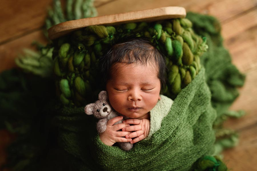 Close up photo of newborn boy wrapped in green holding a brown teddy bear