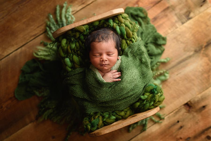 Newborn snuggled in a wooden bed from the original photoblocks on a wood floor