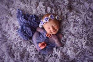 Newborn Portrait of baby smiling swaddled in purple wearing a purple floral crown on purple fur