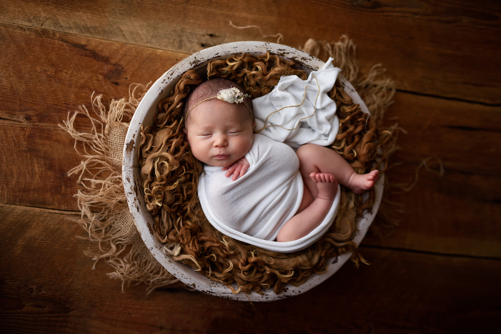 Portrait of asian baby girl wrapped in white in a white bowl