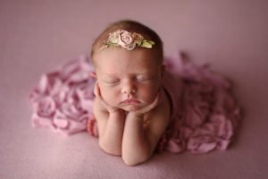 Baby girl photographed by a newborn photographer in Denver posed in the froggy pose all in pink