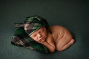 Newborn portrait of baby boy in tushie pose sleeping on a green plaid pillow with a matching sleep hat.