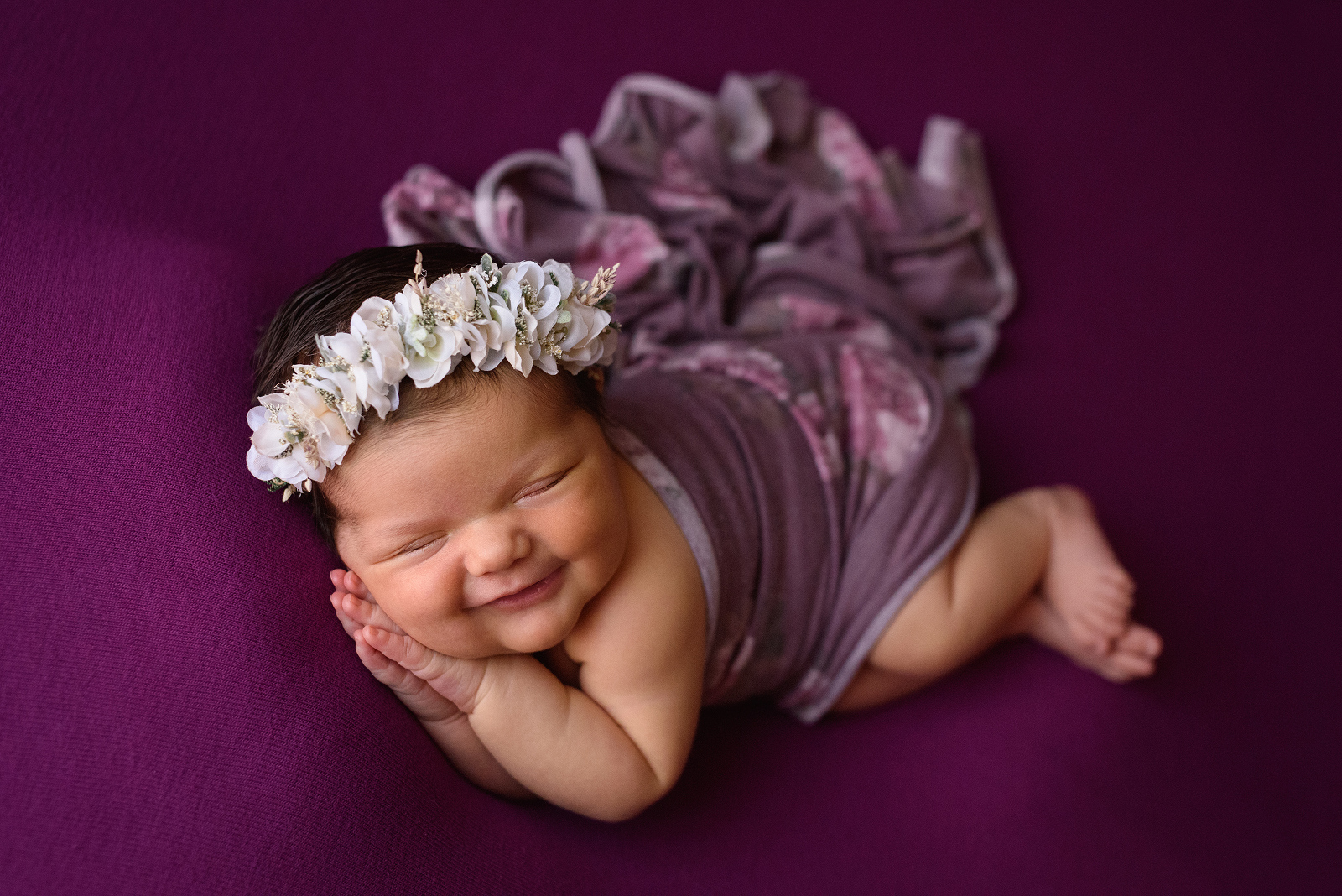 Best photo of baby girl with the biggest smile wrapped in a magenta floral wrap wearing a white floral crown