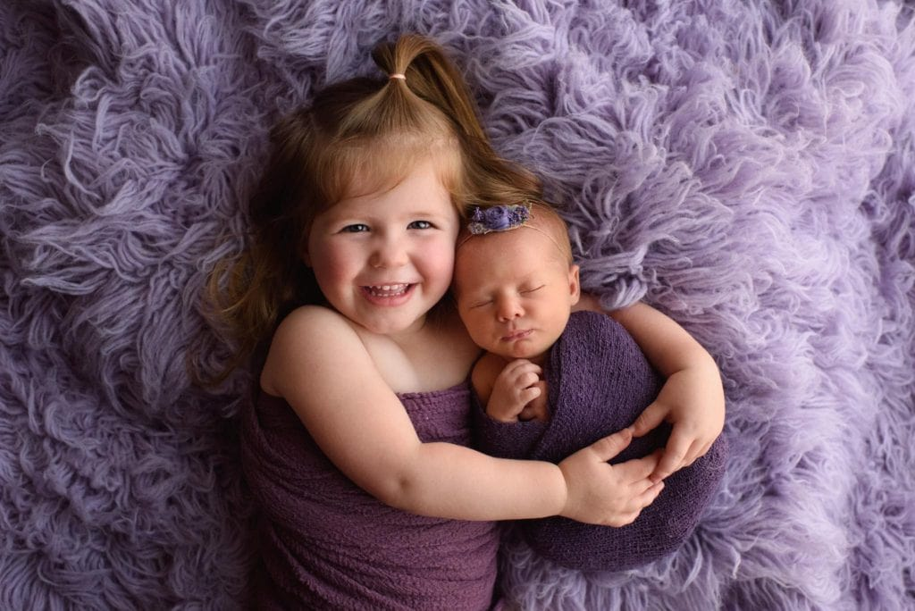 Newborn photography of big sister hugging her new baby sister on purple