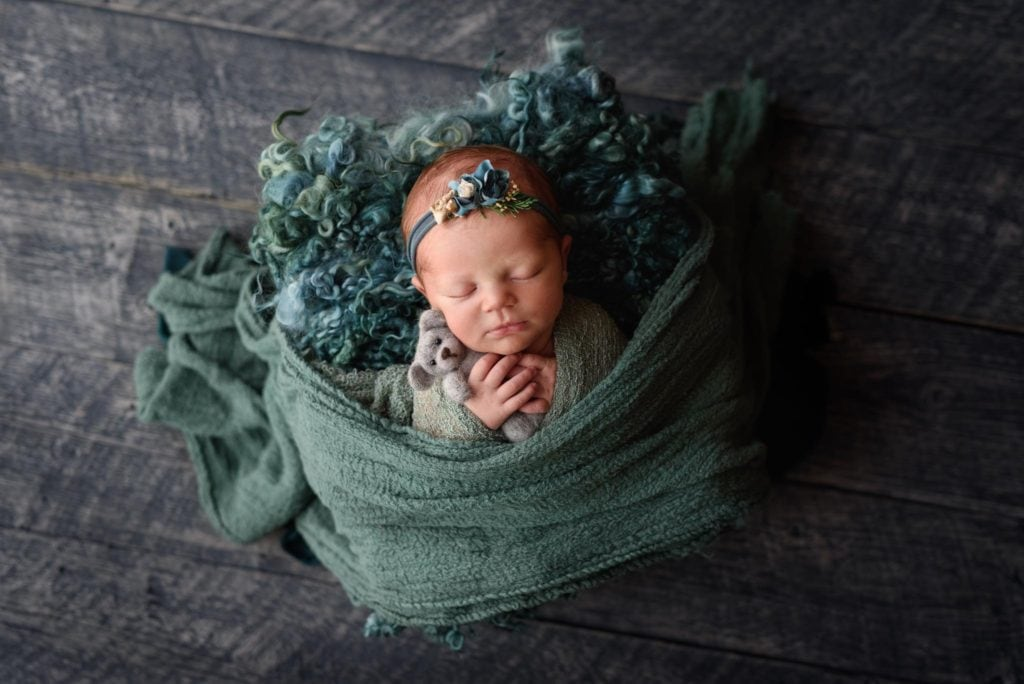 Cutest little baby swaddled in a muted green holding a gray bear from woolley designs.