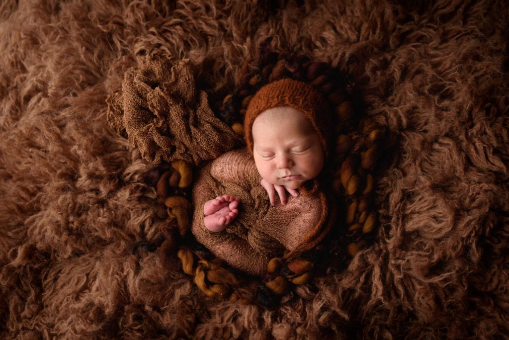 Baby boy wrapped in brown photographed on a cloud of fur