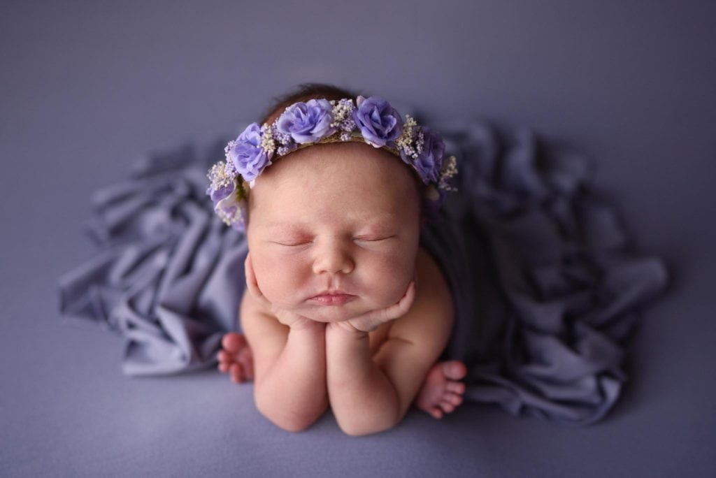 Baby girl in froggy pose wearing a Baby Bliss floral crown on purple