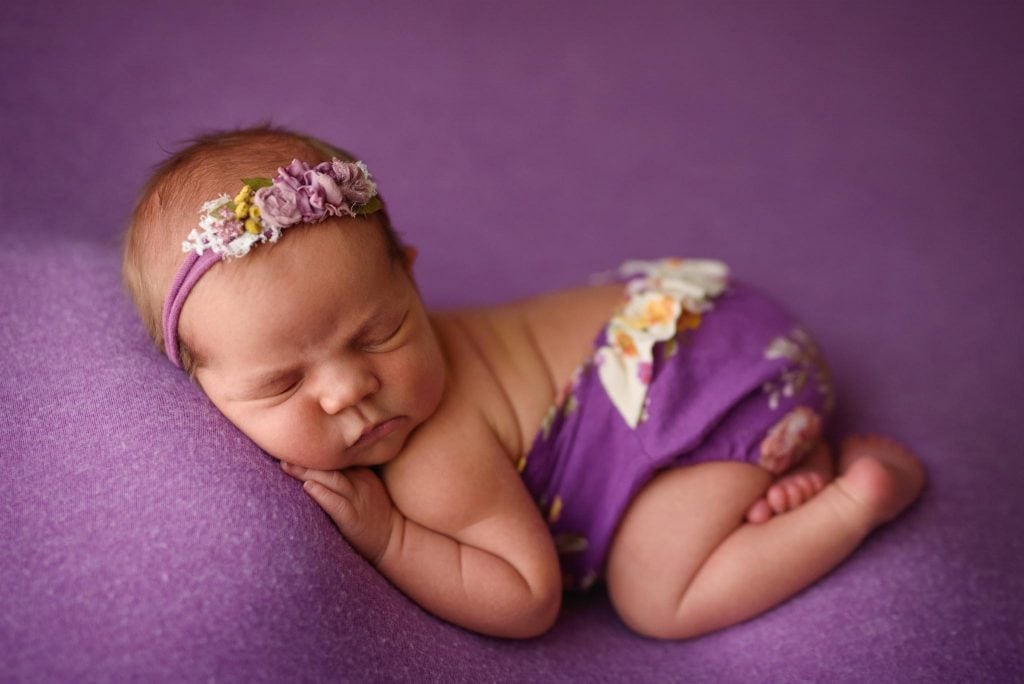 Newborn Photography of baby girl in a purple outfit on purple in tushie pose