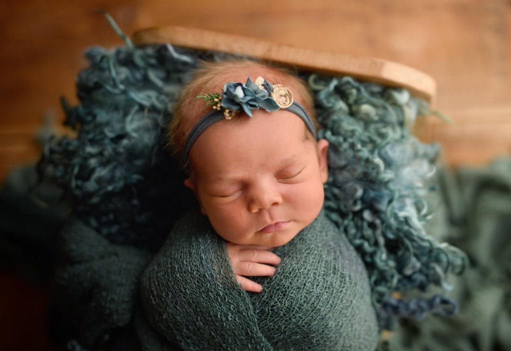Newborn swaddled in teal photographed in a little baby bed.
