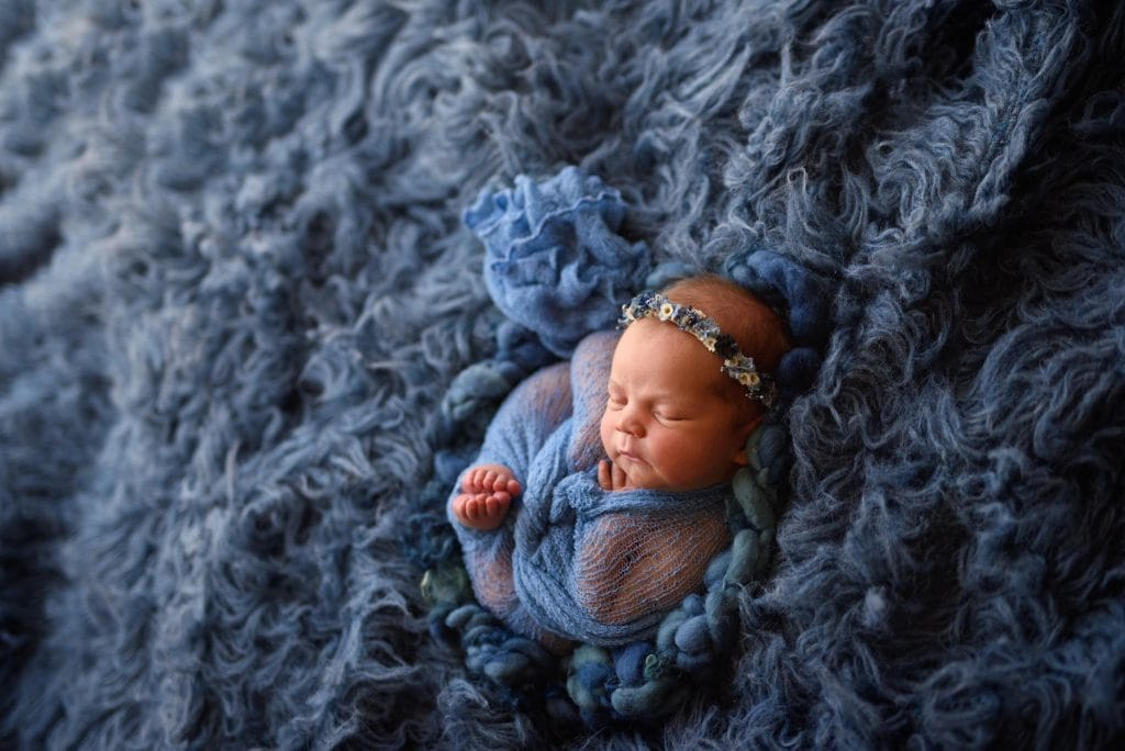 Portrait of baby girl on a cloud of blue