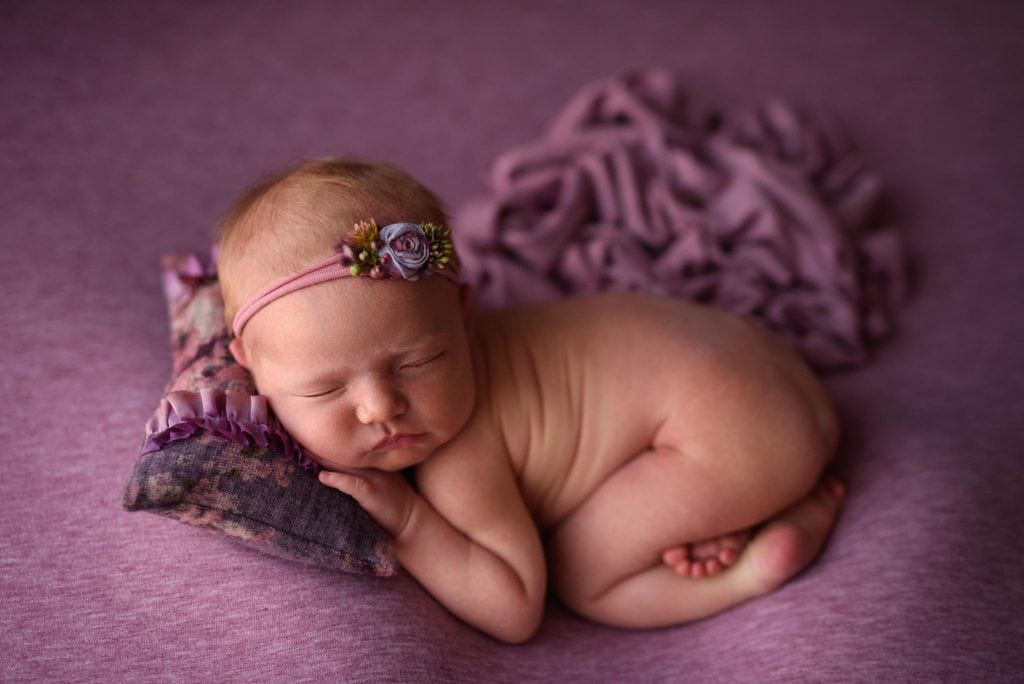 Baby girl sleeping, posed on a purple background with a purple pillow and headband.