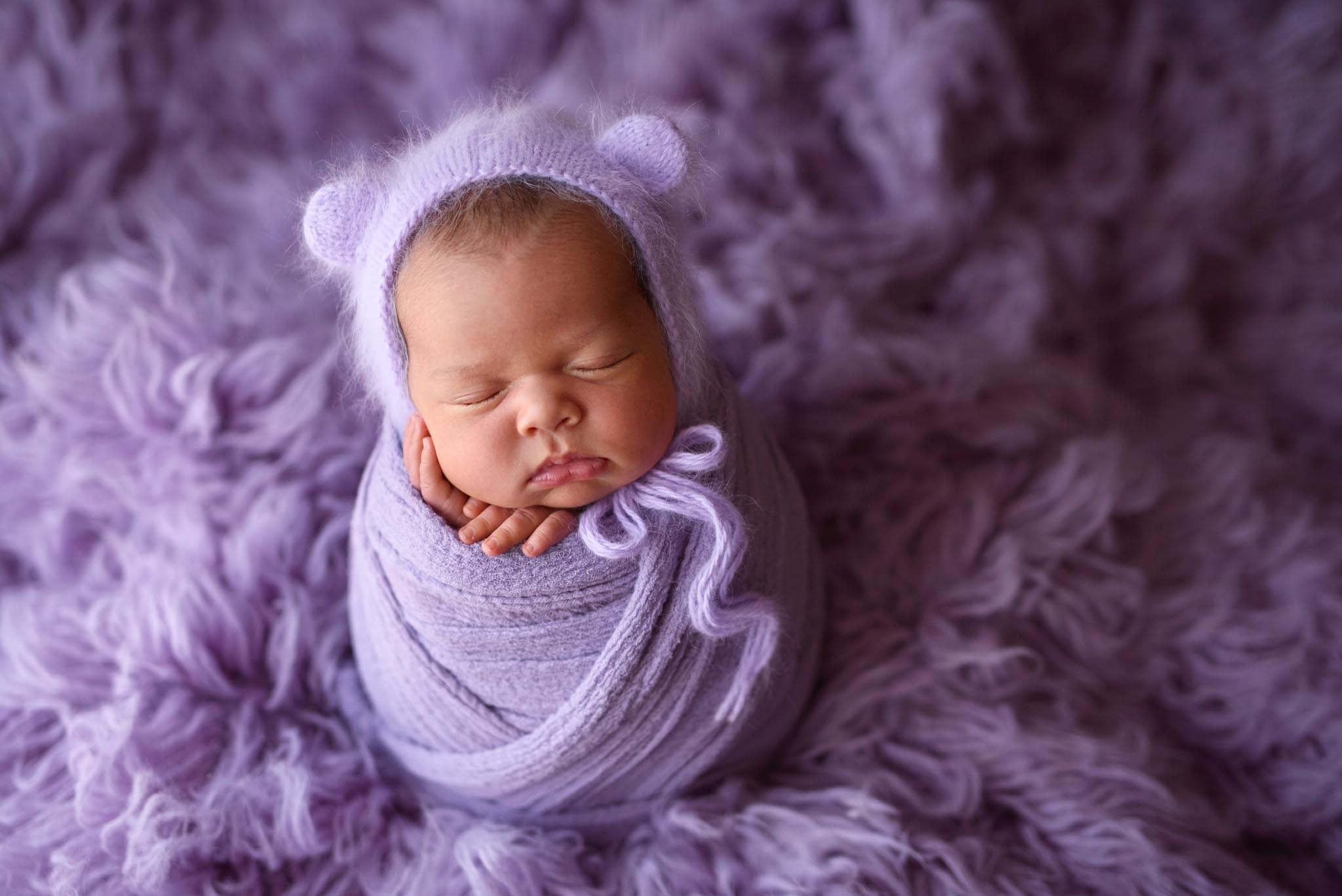 Baby photo of newborn girl swaddled up in purple wearing a purple angora bear hat