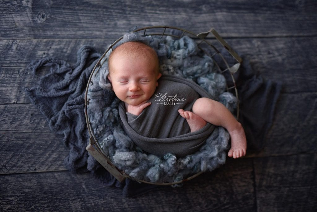 Newborn Photography session in Denver of baby in swaddled in a basket smiling.